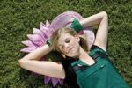 Thumbnail Young woman, gardener, lying on the grass with a flower in her mouth, sunbathing and daydreaming
