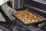 Thumbnail Woman taking baked Christmas cookies out of the oven