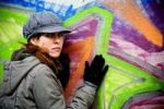 Thumbnail Woman leaning against graffiti-covered wall