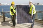 Thumbnail Two people in hard hats and protective jackets carrying a giant solar panel