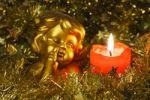Thumbnail Angel figurine beside a burning candle, Christmas decoration