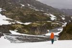 Thumbnail Hiker, backpacker in rain gear, backpack cover, snow bridge, passing canyon near historic Happy Camp, alpine landscape, Chilkoot Trail, Chilkoot Pass, Klondike Gold Rush, Yukon Territory, British