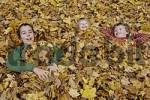 Thumbnail three children lying amused between leaves in autumn