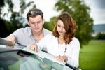 Thumbnail Young couple looking at a road map on a car