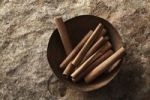 Thumbnail Cinnamon sticks (Cinnamomum) in a copper bowl on a stone surface