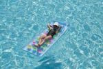 Thumbnail Girl, eight years, relaxing on air mattress in the pool