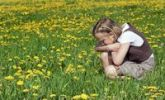 Thumbnail 8-year-old girl sitting on a meadow observing nature