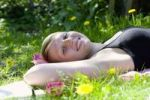 Thumbnail A young woman lying on her back in a meadow