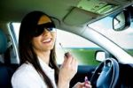 Thumbnail Young woman putting on makeup in the car