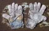 Thumbnail Pair of badly worn work gloves on rusty metal plate