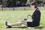 Thumbnail Businesswoman sitting on lawn, using laptop