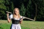Thumbnail Farm girl with a scythe, wearing a dirndl, a traditional German or Austrian dress