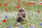 Thumbnail Little girl sitting in a wildflower meadow