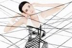 Thumbnail Woman, 24, dressed in the style of the 60s, standing between spanned threads, symbolic image network