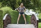Thumbnail Young woman wearing hot pants, leopard-print top and high heels posing confidently on curved wooden bridge
