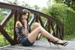 Thumbnail Young woman wearing hot pants, leopard-print top and high heels sitting down by the wooden balustrade of a wooden bridge