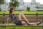 Thumbnail Young woman wearing hot pants, a leopard-print top and high heels, posing on a bench