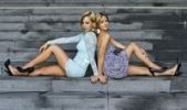 Thumbnail Two young women in short dresses and high heels posing while sitting on stone stairs