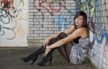 Thumbnail Young woman with dark hair wearing a top with a zebra pattern and high heels posing while sitting in front of a wall with graffiti