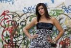 Thumbnail Young woman with dark hair wearing a top with a zebra pattern and posing in front of a wall with graffiti