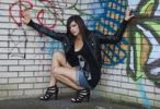 Thumbnail Young woman with dark hair wearing hot pants, a black leather jacket and high heels posing in front of a wall with graffiti