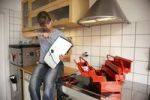 Thumbnail Young woman repairing a toaster in the kitchen