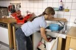 Thumbnail Young woman repairing a defective water faucet in a kitchen