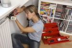 Thumbnail Young woman repairing the thermostat of a radiator