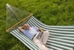 Thumbnail Elderly gentleman lying in a hammock with a netbook