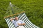 Thumbnail Elderly gentleman lying in a hammock and listening to music