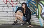 Thumbnail Dark-haired young woman wearing hot pants, a black leather jacket and high heels posing in front of a wall with graffiti