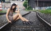 Thumbnail Dark-haired young woman wearing a beige dress and high heels posing while sitting on a railway track