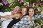 Thumbnail Portrait of a mother with two thirteen-year-olds girls in front of flowers