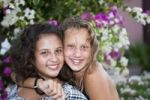 Thumbnail Portrait of two thirteen-year-olds girls in front of flowers