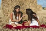 Thumbnail Two young women sitting on a harvested grain field in front of a bale of straw and talking, Finistere departement, Brittany region, France, Europe