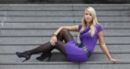 Thumbnail Young blonde woman wearing a purple dress and high heels posing while sitting on a stone staircase