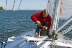 Thumbnail Fisherman aboard a sailing yacht gutting a freshly caught pike, Baltic Sea, Germany, Europe
