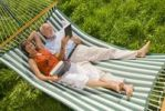 Thumbnail Senior citizen couple lying in a hammock, woman wearing a headset looking at a netbook or laptop, man reading a book
