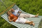 Thumbnail Senior citizen couple lying in a hammock, woman listening to music, man reading a book