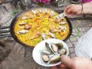 Thumbnail Cook preparing a paella, a Spanish rice dish, adding mussels, series, no. 4