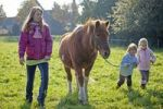 Thumbnail Young girls walking with a pony