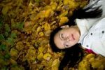 Thumbnail Young woman lying in autumn leaves