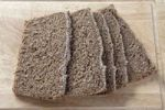 Thumbnail Slices of whole grain bread on a wooden board