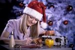 Thumbnail A girl with Santa Claus hat writing Christmas mail in front of a Christmas tree
