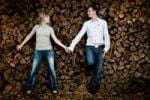 Thumbnail Young couple, hand in hand, leaning against a wood pile