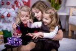 Thumbnail Three girls unpacking Christmas gifts