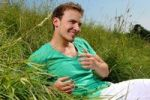 Thumbnail Young man lying in tall grass, smiling, sunbathing