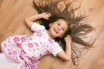 Thumbnail Girl, 4 years, lying on the floor, laughing