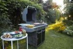 Thumbnail BBQ area with large barbecue, salads and side dishes in the garden in the evening