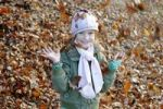 Thumbnail Girl playing with leaves in autumn